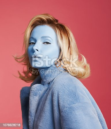 Woman with blue skin make-up and wearing blue faux fur coat