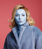 Woman with blue skin wearing blue coat