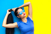 Woman with blue sunglasses and casual clothes posing in front of blue and yellow wall background.