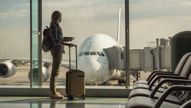 Woman with boarding passes and hand baggage looks out the terminal window on a large airliner Woman with boarding passes and hand baggage looks out the terminal window on a large airlinerStart of the journey. carry on luggage stock pictures, royalty-free photos & images