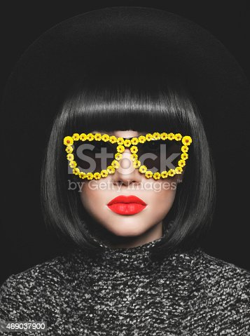 469211680 istock photo Woman with bobbed black hair and yellow sunglasses 469037900