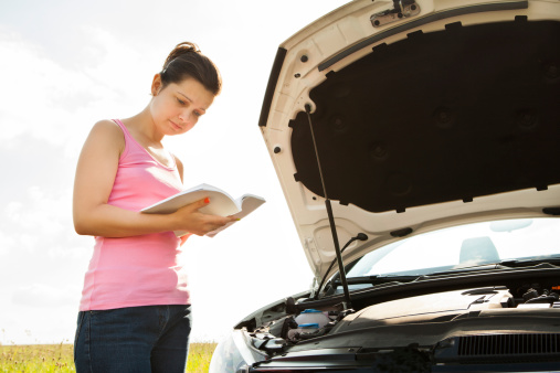 istock Woman With Book In Front Of Car 464579695