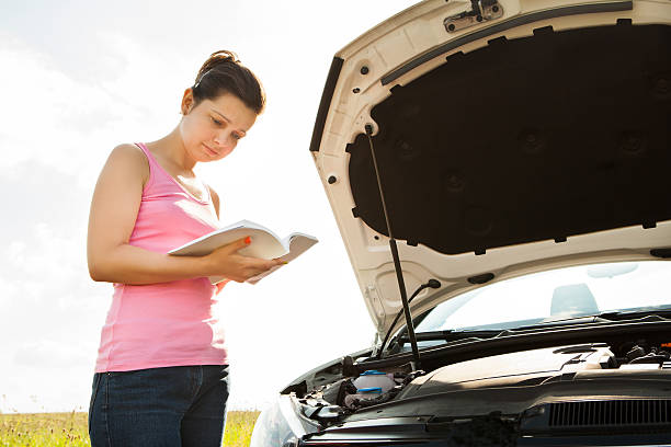 Woman With Book In Front Of Car stock photo