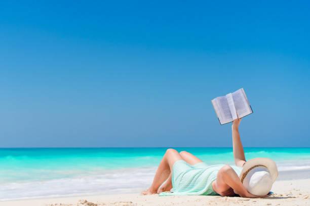 Frau mit Buch am Meer liegend – Foto