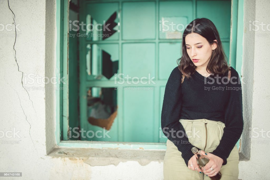 Woman with bottle of alcohol drink standing next to old ruined house. royalty-free stock photo