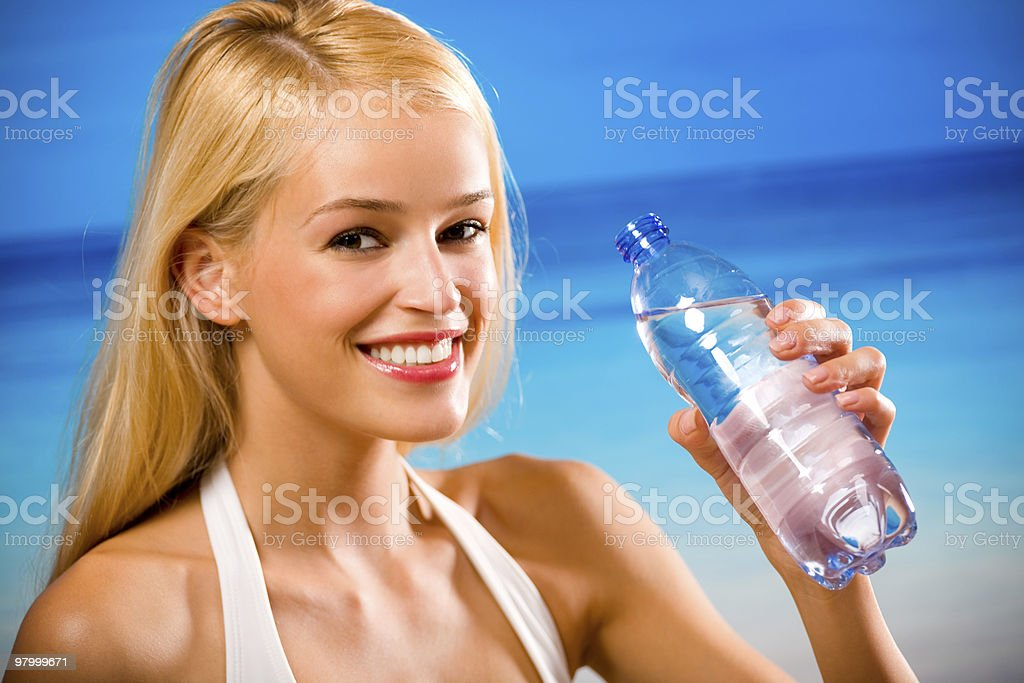 Woman with bottle of water in swimwear on beach royalty-free stock photo