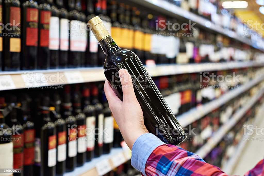 Woman with bottle of wine in store stock photo