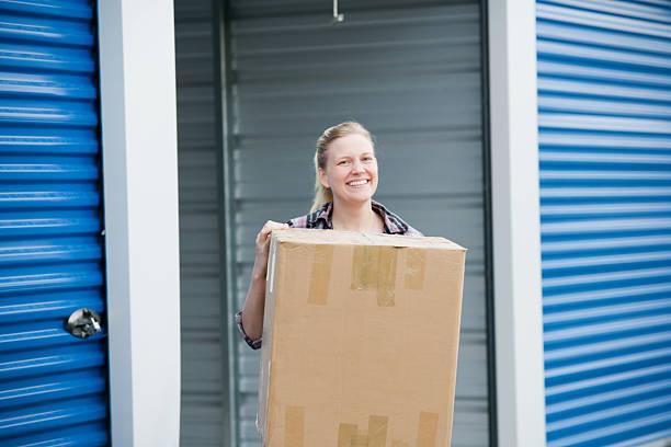 Woman With Box Outside Self Storage Unit stock photo