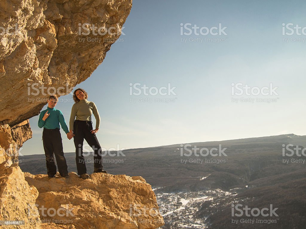 Woman with boy standing on a rock stock photo