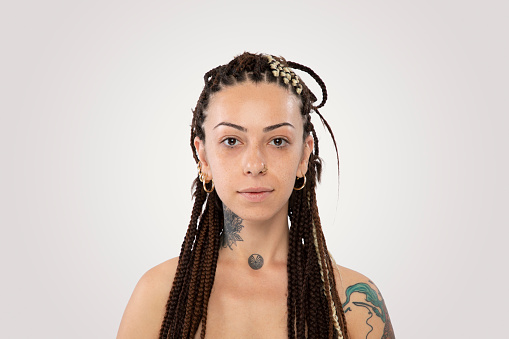 Stylish woman with braided hair and tattoo over white background