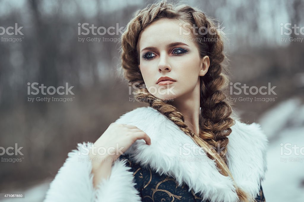Woman with braided hair in fur cloak looking into distance stock photo