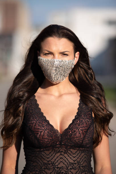Woman with breast in neckline wearing trendy violet fashion face mask stock photo
