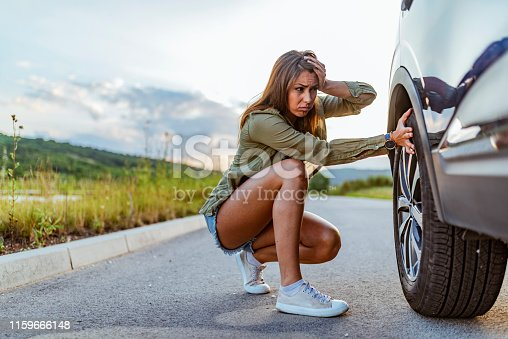 104275470istockphoto Woman with broken down car flat tire 1159666148