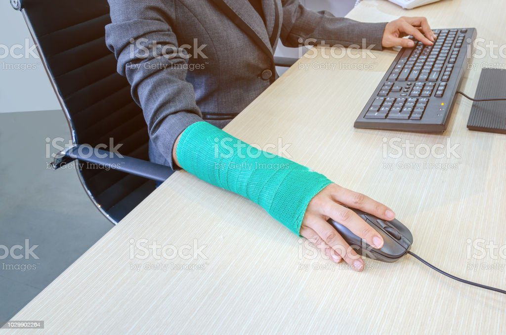 Woman With Broken Hand And Green Cast Working On Computer In
