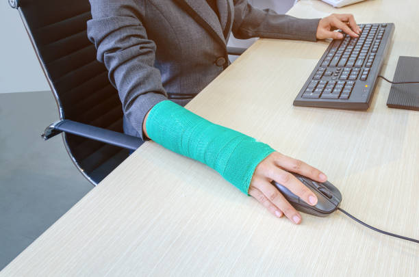 woman with broken hand and green cast  working on computer in office. stock photo
