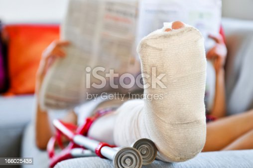 Woman with broken leg is lying on the sofa and reading newspaper.