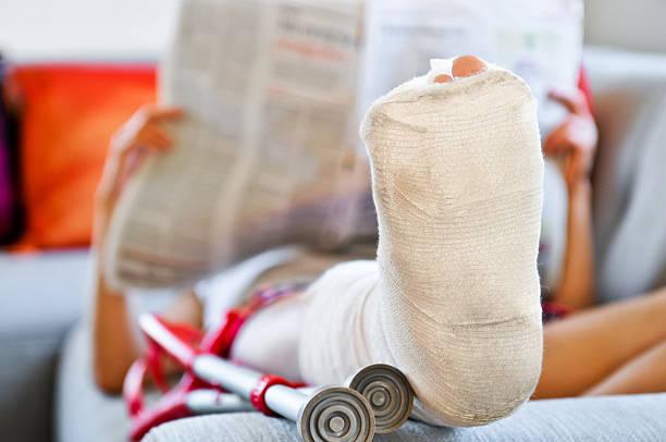Frau mit gebrochenen Bein Lesen auf dem sofa liegende und Tageszeitung – Foto