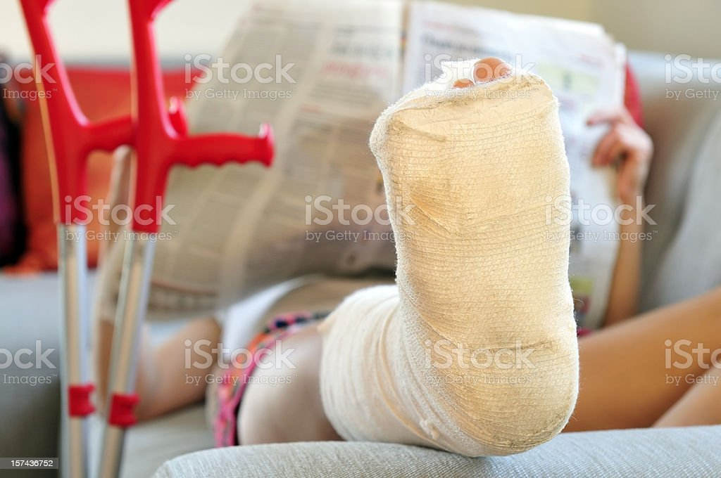 Woman with broken leg lying on sofa, bandage and crutches royalty-free stock photo