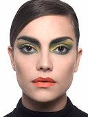 woman with brown eyes green and yellow eyeshadowand orange lipstick