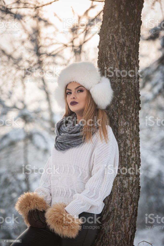 Frau mit brauner Pelzmütze und Jacke genießen den Winter. Seitenansicht der modischen blonden Mädchen posiert gegen schneebedeckte Brücke. Junges Weibchen mit kaltem Wetteroutfit – Foto