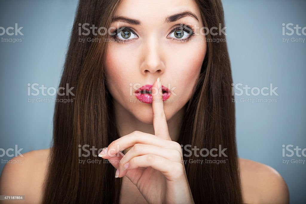 Woman with brown hair with fingers on lips stock photo