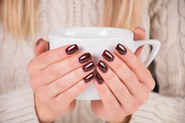 frau mit braunen lackieren hält kaffee in händen - herbst nagellack stock-fotos und bilder