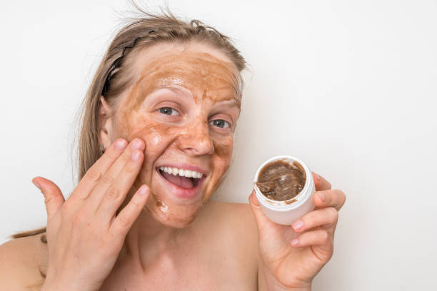 Woman with brown volcanic mask on her face stock photo