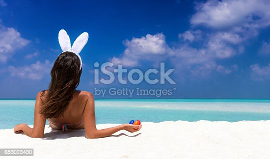istock Woman with bunny ears and colorful easter eggs on a beach 653023430