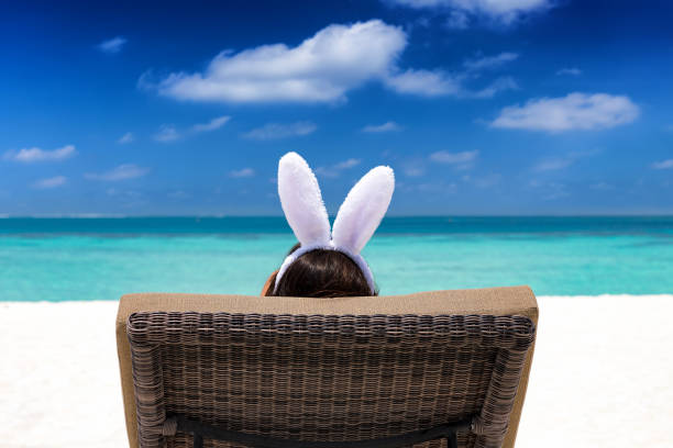 woman with bunny ears on a tropical beach - easter stock pictures, royalty-free photos & images