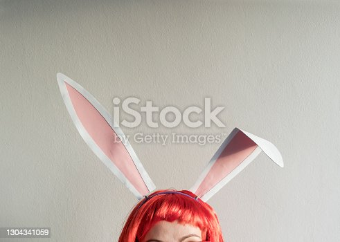 istock Woman with bunny ears peeking 1304341059