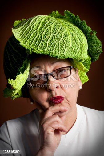 portrait of a senior woman with a hat of savoy cabbage