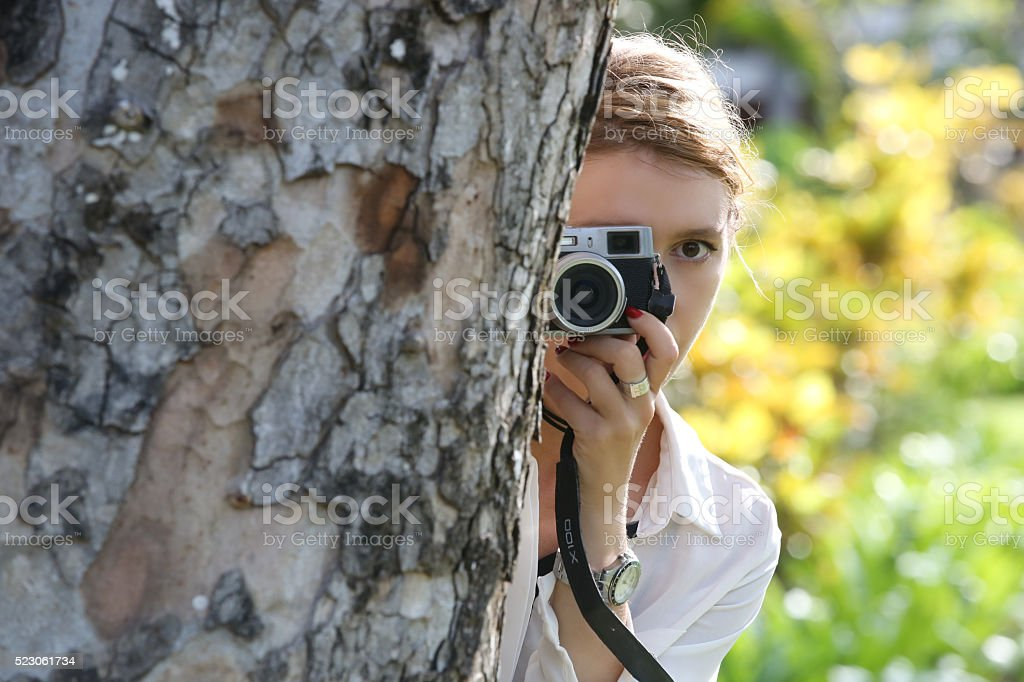 Woman with camera hiding behind the tree stock photo