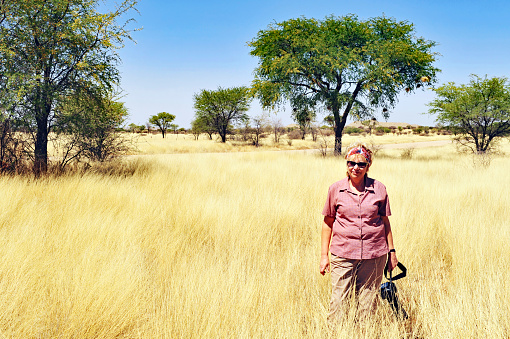 Woman with camera standing amongst golden grasses ,Namibia