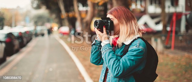 Woman with camera taking picture in the street