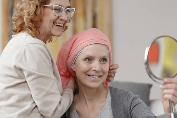 Woman with cancer in headscarf Happy woman with cancer in pink headscarf looking in the mirror while mother smiling headscarf stock pictures, royalty-free photos & images