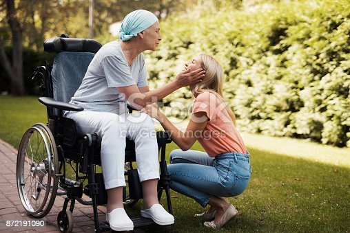 istock A woman with cancer is sitting in a wheelchair. She smiles and holds her daughter's cheeks. 872191090