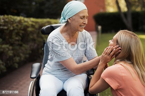 istock A woman with cancer is sitting in a wheelchair. She smiles and holds her daughter's cheeks. 872191166