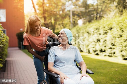 istock A woman with cancer is sitting in a wheelchair. She walks on the street with her daughter and they are having fun. 872188240