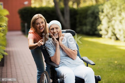 istock A woman with cancer is sitting in a wheelchair. She walks on the street with her daughter and they are having fun. 872188270