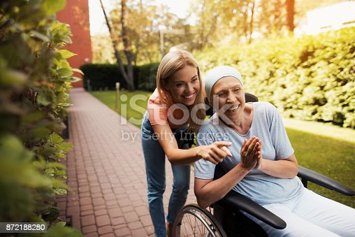 istock A woman with cancer is sitting in a wheelchair. She walks on the street with her daughter and they are having fun. 872188280