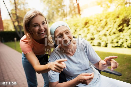 872191096 istock photo A woman with cancer is sitting in a wheelchair. She walks on the street with her daughter and they are having fun. 872191088