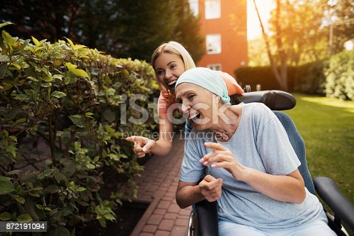 istock A woman with cancer is sitting in a wheelchair. She walks on the street with her daughter and they are having fun. 872191094