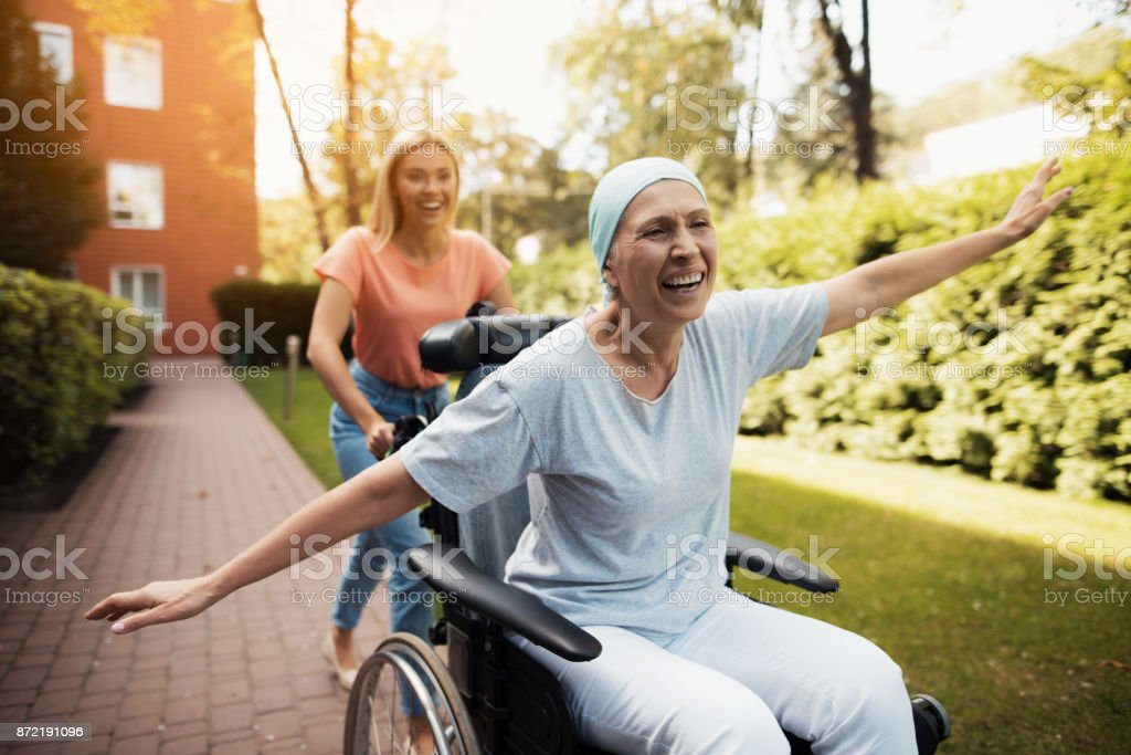 A woman with cancer is sitting in a wheelchair. She walks on the street with her daughter and they fool around. stock photo