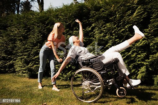 istock A woman with cancer is sitting in a wheelchair. She walks on the street with her daughter and they fool around. 872191164
