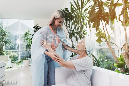 872191096 istock photo A woman with cancer is sitting on a white sofa in a modern clinic. Her daughter came to see her. 872187908
