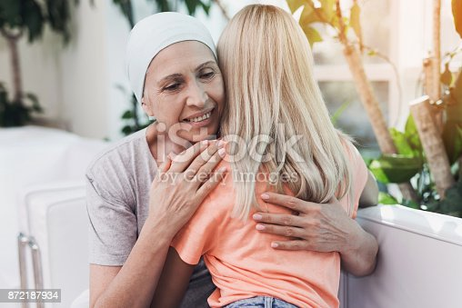 istock A woman with cancer is sitting on a white sofa next to her daughter. A girl is hugging a woman 872187934