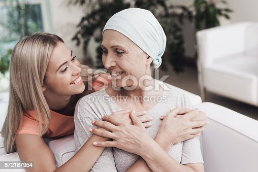 istock A woman with cancer is sitting on a white sofa next to her daughter. A girl is hugging a woman 872187954