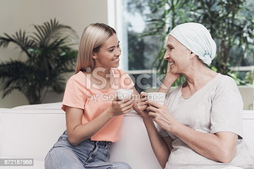 istock A woman with cancer is sitting on a white sofa next to her daughter. They sit with cups of tea in their hands. 872187988