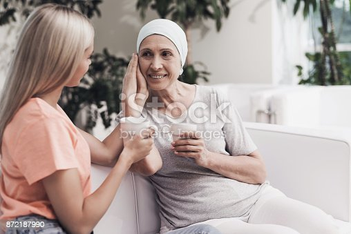 872191096 istock photo A woman with cancer is sitting on a white sofa next to her daughter. They sit with cups of tea in their hands. 872187990