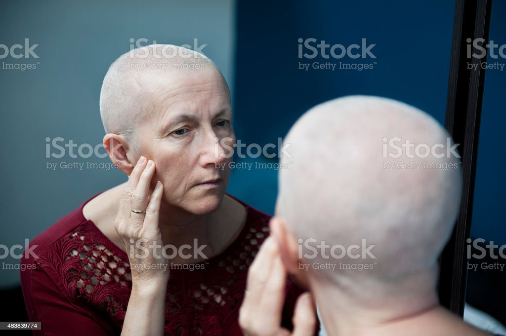 Woman with Cancer Looking in Mirror stock photo